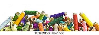sewing threads - random row of colorful threads on bobbins;...