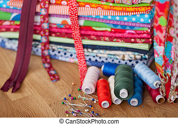 A variety of sewing utensils like pins, thread, ribbon and zipper.