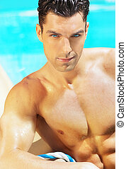 Sexy shirtless handsome male model with sparkling blue eyes against blue swimming pool background