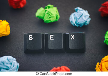 The word Sex on a black background with some colorful crumpled paper balls around it