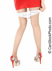 Close up behind - the girl puts on the shorts, isolated