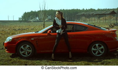 Sexual young lady in black business suit stands in the field with a red sports car