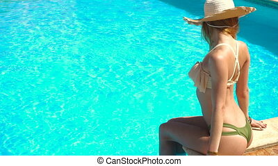 sexual young lady in straw hat and seductive swimsuit sits by the blue pool