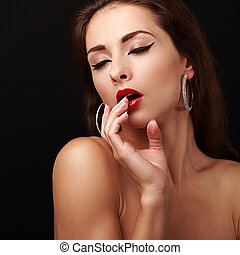 Sexual young woman with finger near red lips. Closeup art portrait