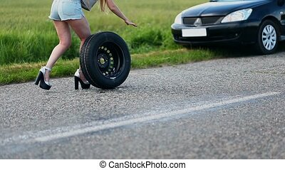 Sexually dressed woman is rolling spare wheel on rural road to change flat tyre