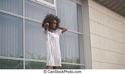 Sexy african american business lady in short seductive dress posing at the glass office wall. Camera movement