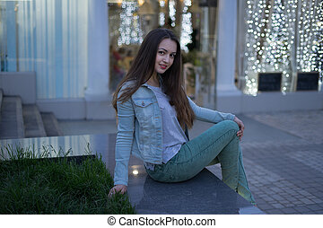 Sexy alone girl sitting on the garden bed and looking at the camera