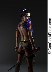 Sexy amazon with dreadlocks and sword rearview
