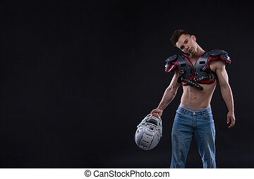 American football player with helmet in hand on black background
