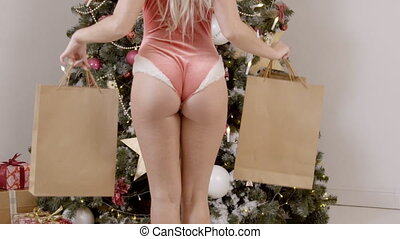 Sexy ass of young female Santa, who is standing with paper bags near the Christmas tree, slow motion.
