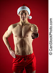 Sexy athletic macho in santa claus hat. If you were very bad girl. Macho sexy muscular torso posing confidently. Santa claus comes not only to good girls. Athlete man wear santa hat and red shorts