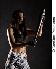 sexy athletic woman with baseball bat on dark background in the beam of a searchlight