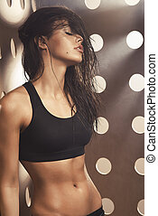 Sexy attractive slim woman with perfect fitness body posing over background with holes and smoke.