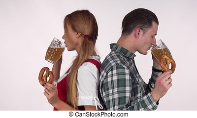 Sexy Bavarian woman and her man enjoying beer with pretzels....