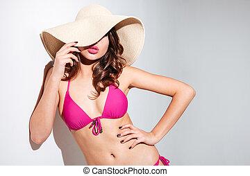 Sexy beach girl in hat wearing bikini over white background