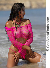Sexy beach girl posing in fishnet top on beach