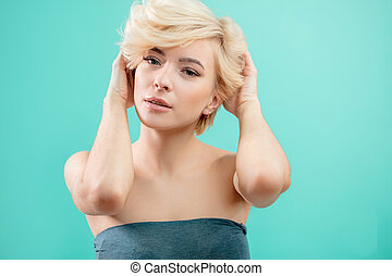 beautiful blond woman with short hair touching her hair on blue background.