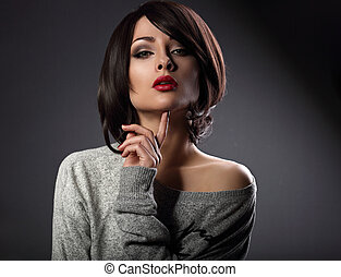 Sexy beautiful makeup woman with short hair style, red lipstick touching her face on dark shadow background. Closeup