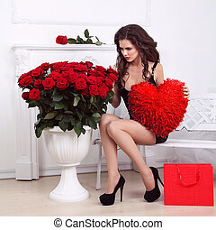 Sexy beautiful woman holding red heart and bouquet of roses . Valentine day love concept