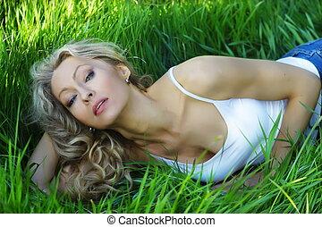 Sexy beautiful woman lying on grass