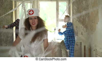Sexy beautiful young female woman nurse screams and shouts at patients in psychiatric hospital. Psychos catch the doctor in room in mental clinic. Mad crazy people tie up by bandages their doctor.