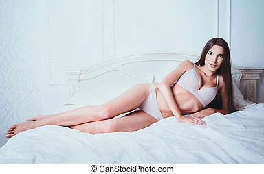 Sexy beautiful young woman in underwear lying on bed