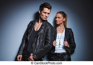 biker pose looking away while his woman is starring at him