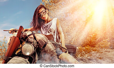 Sexy biker woman on the autumn background.
