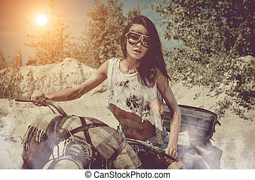 Sexy biker woman on the desert background.