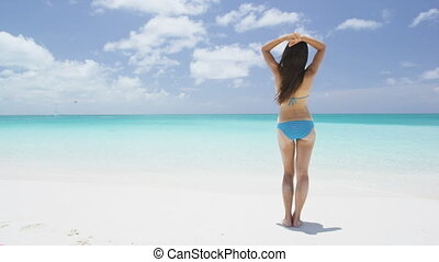Bikini woman with slim sexy body standing from behind on tropical white sand beach in Caribbean looking over the perfect turquoise ocean. Luxury living vacation destination. SLOW MOTION, RED EPIC.