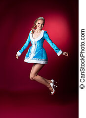 Sexy blond christmas girl in blue jump on red