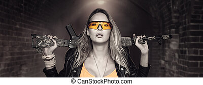 Sexy blond dangerous woman with automatic rifle
