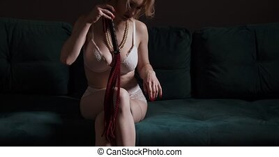 Sexy blond dominant woman in white lingerie sitting and touching herself with a whip.