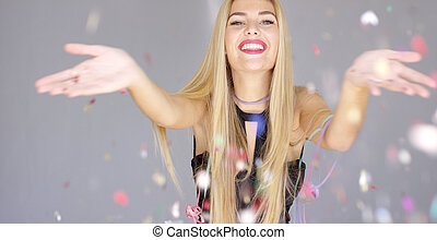 Sexy, blond girl blowing confetti to camera direction -...