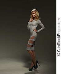 Sexy blond lady in grey dress on dark background