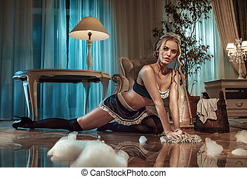 Sexy blond maid cleaning floor in the stylish interior