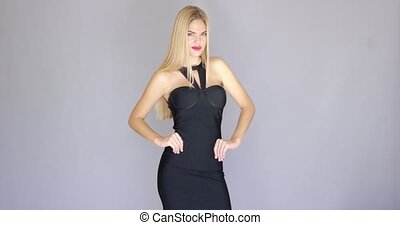 Sexy blond model posing in evening dress over gray