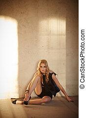 Sexy blond woman in black dress.