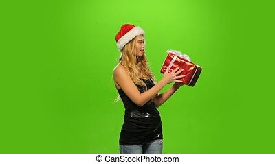 sexy blond woman in Christmas cap with gift. green screen. Slow motion