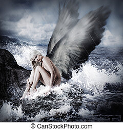 Sexy beautiful blond woman with angel wings sitting on a rock in the sea in storm