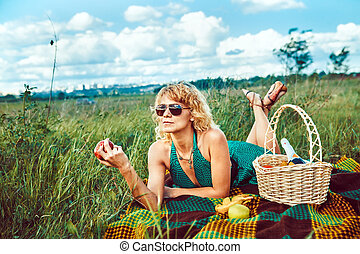 Sexy blond woman with the apple on the picnic.