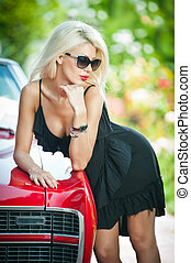 Sexy blonde bent over red car