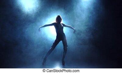 Sexy blonde dancer in underwear. Silhouette in smoky, slow motion
