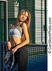 Sexy blonde fitness model with perfect long hair posing with a tennis racket at the court