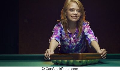 Sexy blonde girl playing Russian billiards.