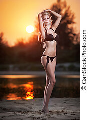 Sexy blonde in bikini in sunset