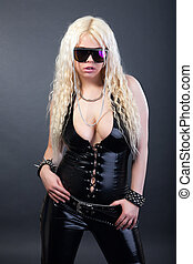 Sexy blonde in latex suit and sunglasses on black background