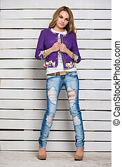 Sexy blonde in ripped jeans and purple jacket posing near...