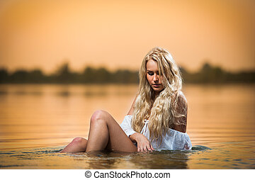 Sexy blonde in water at sunset