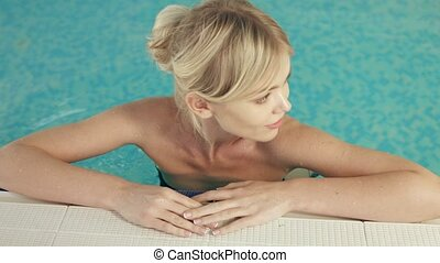 Sexy blonde relaxing in the swimming pool